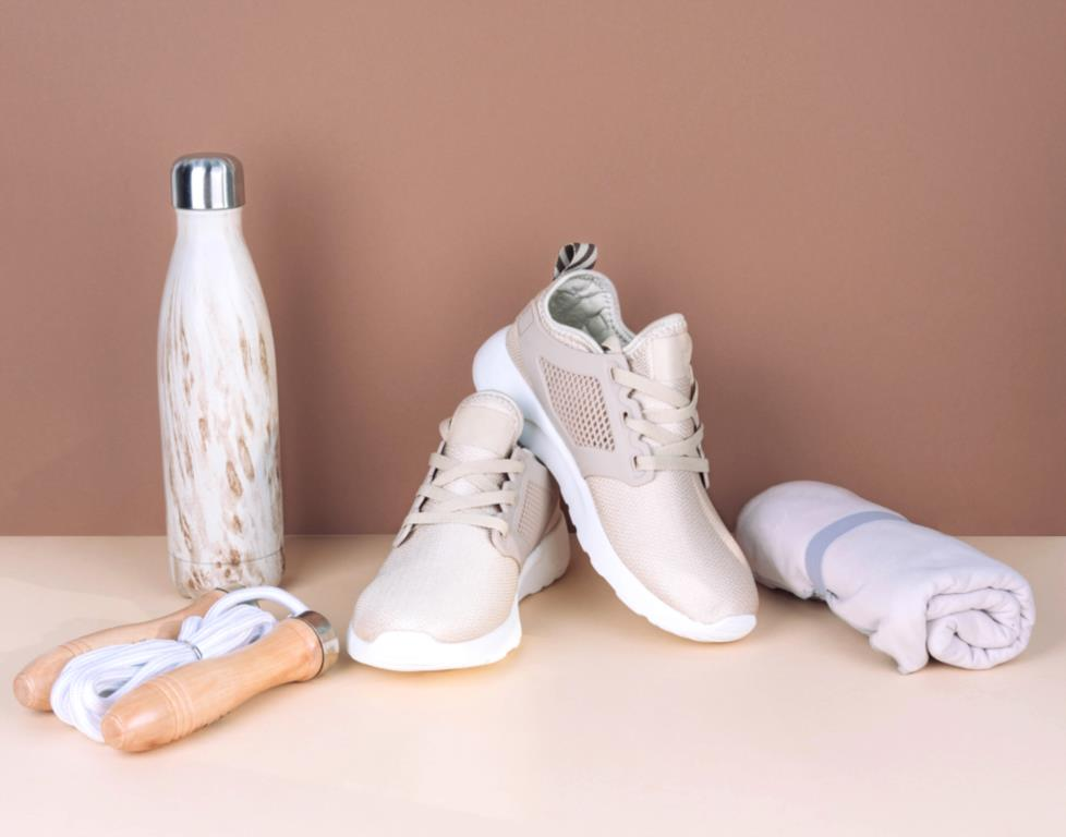 Flat lay of exercise equipment including sneakers a skipping rope a water bottle and towel.