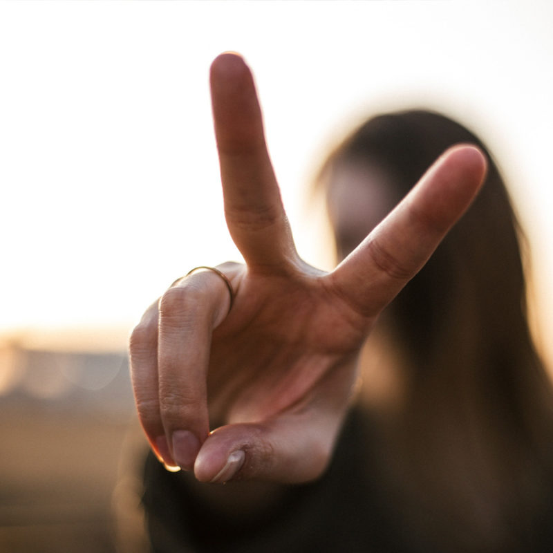 woman holding up peace sign