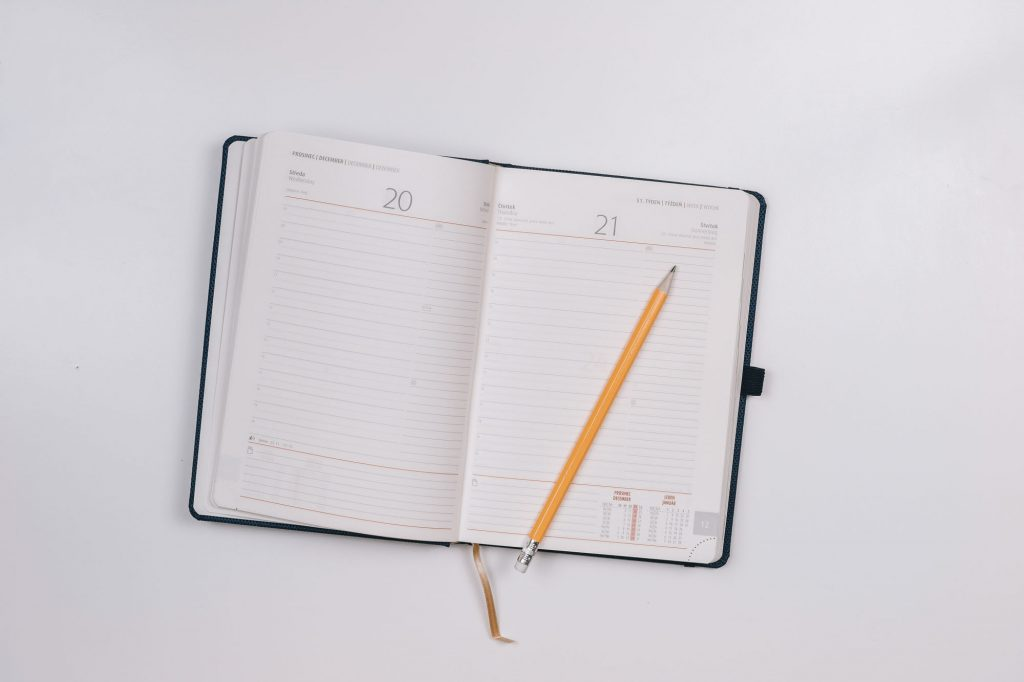 Pencil inside white diary. get organised image.