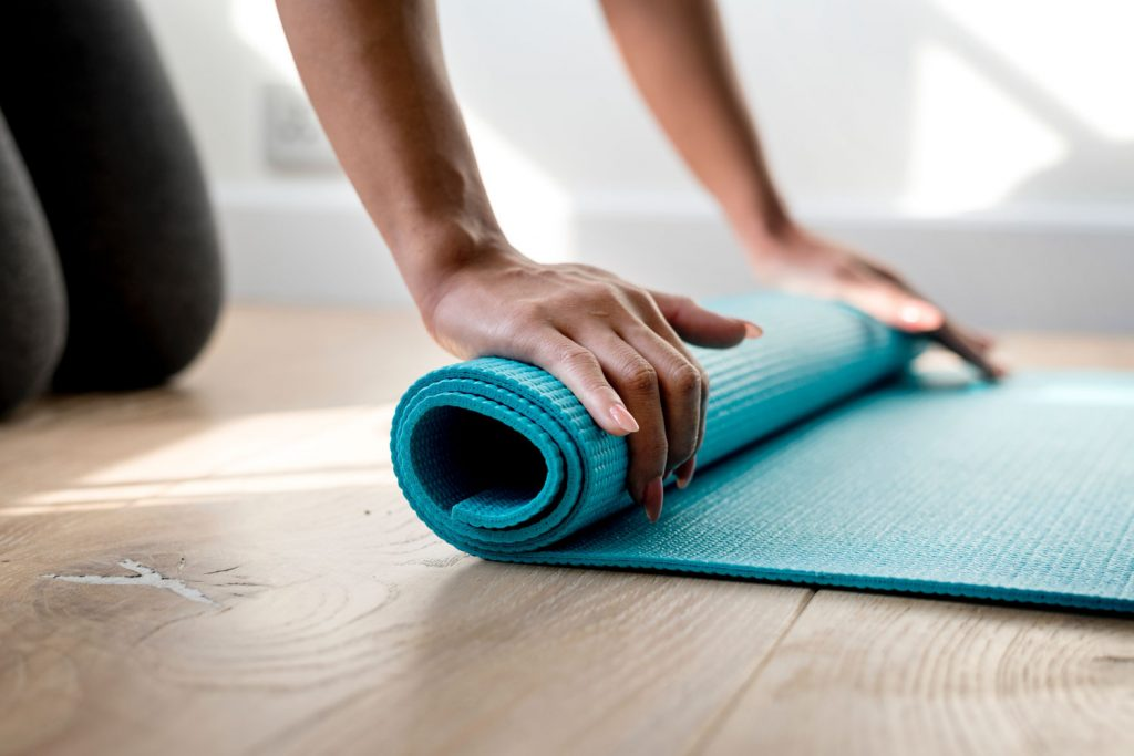Woman rolling out Yoga mat
