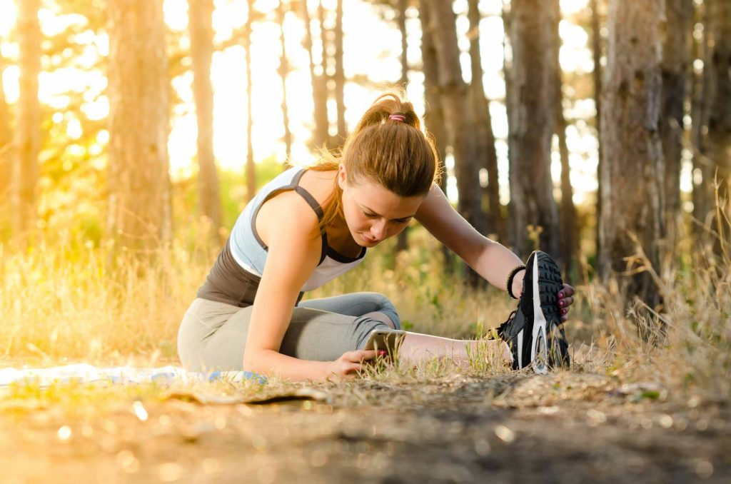 woman stretching outside while doing her morning workout.