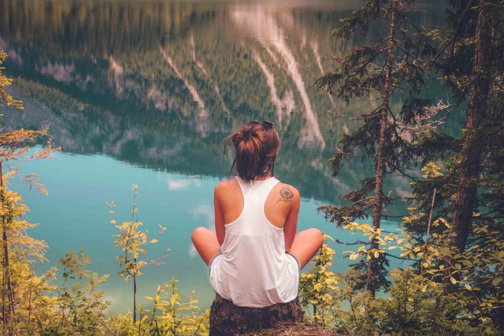 young woman in nature meditating wearing white