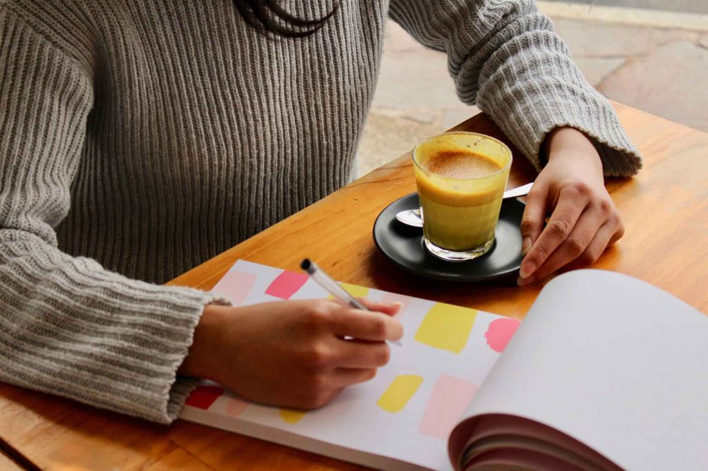 Woman writing in notebook drink a tumeric latte inside a cafe