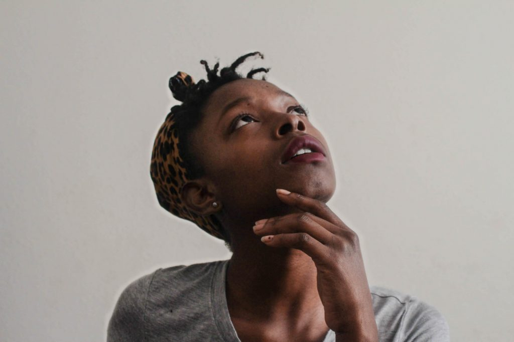 Girl looking upward with her hand on her chin thinking